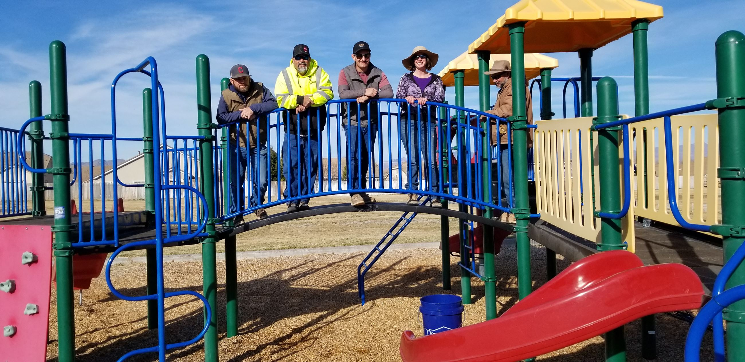 Parks Crew Standing on the Bridge of a Play Structure